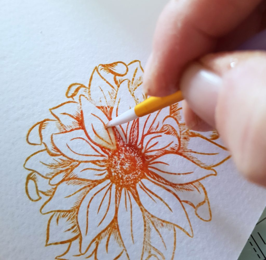 A fine brush adding colour detail to a stamped flower using the Spectrum Noir Water-Reactive Inkpads