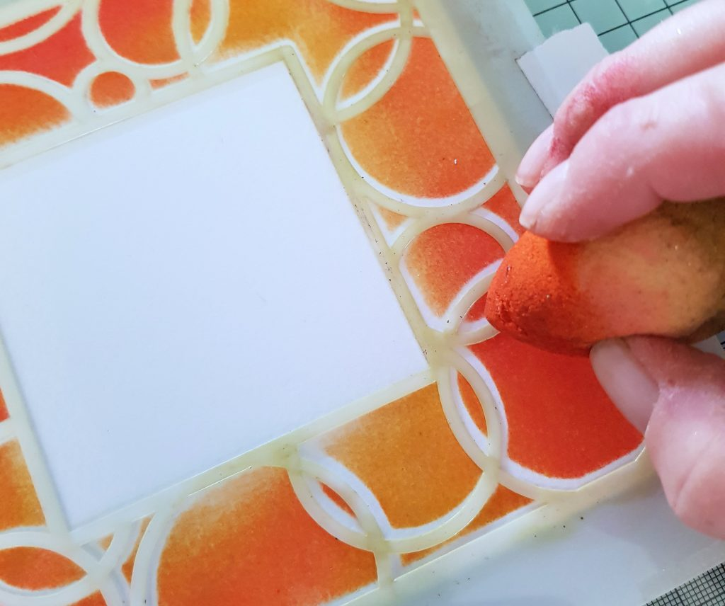 A fiery red and orange border on a card with stencil detailing using the Spectrum Noir Water-Reactive Inkpads